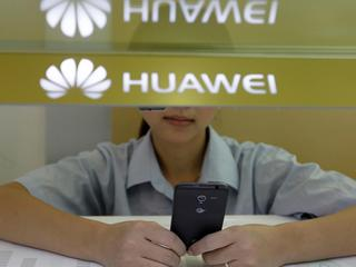 FILE PHOTO: A sales assistant looks at her mobile phone as she waits for customers behind a counter at a Huawei booth in Wuhan