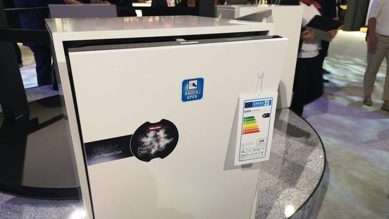 Miele przedstawia nową zmywarkę. Ten mod otwiera się dwoma puknięciami palca w drzwi. Do zmywarki wsadzamy duży zbiornik detergentu, z którego potem urządzenie pobiera tyle środka czysczącego, ile trzeba. Oczywiście ten zbiornik sprzedaje tylko Miele (ale można używać zwykłych kapsułek)