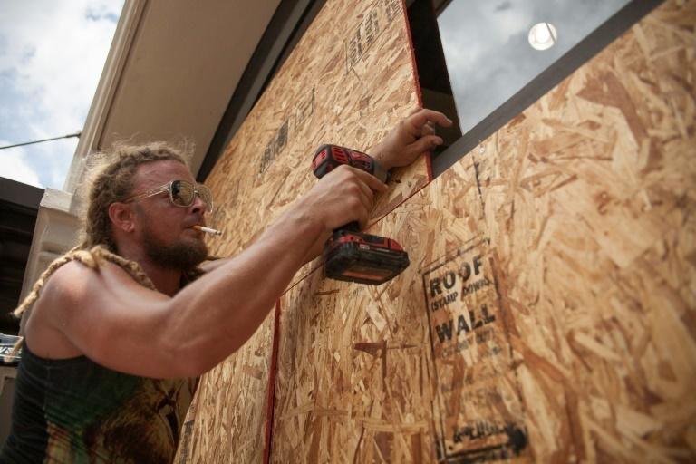Matt Harrington boards up a Vans shoe store near the French Quarter in New Orleans as tropical storm Barry approaches