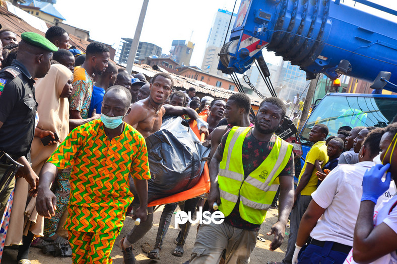 A corpse being taken away from the site of the collapsed building (Pulse)