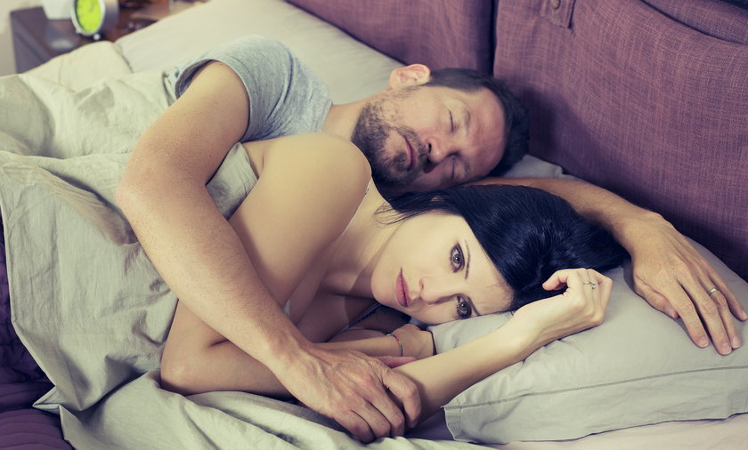 Smutna kobieta leżąca w łóżku z mężczyzną