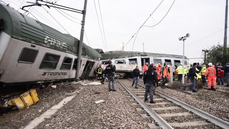 Dwa wagony, stojące przechylone w poprzek torów, są częściowo zmiażdżone.