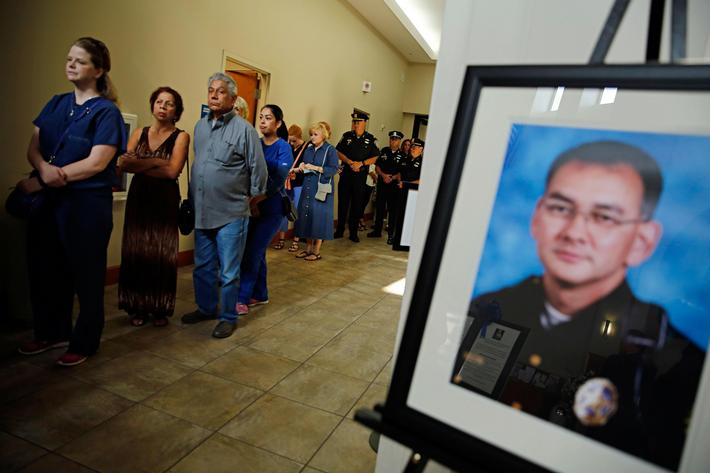 People stand by a photo of slain Dallas police officer Michael Smith as they wait to enter the churc