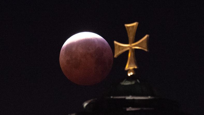 Całkowite zaćmienie Księżyca rozpoczęło się w poniedziałek o godz. 5:41 i trwało do 6:43. W tym czasie Księżyc przybrał barwę czerwoną. Dlaczego tak się dzieje? W trakcie zaćmienia całkowitego Ziemia blokuje docieranie promieni słonecznych bezpośrednio do Księżyca. Jednak nasza planeta ma atmosferę, która załamuje i rozprasza bieg promieni słonecznych. W związku z tym mimo wszystko do Księżyca dociera trochę światła. Jest ono jednak przefiltrowane przez atmosferę, która skuteczniej rozprasza światło o falach krótszych (niebieskie) niż dłuższych (czerwone). Skutki przejścia światła słonecznego przez grubą warstwę atmosfery możemy zobaczyć codziennie na przykład przy zachodzie Słońca – ma ono wtedy kolor czerwony.