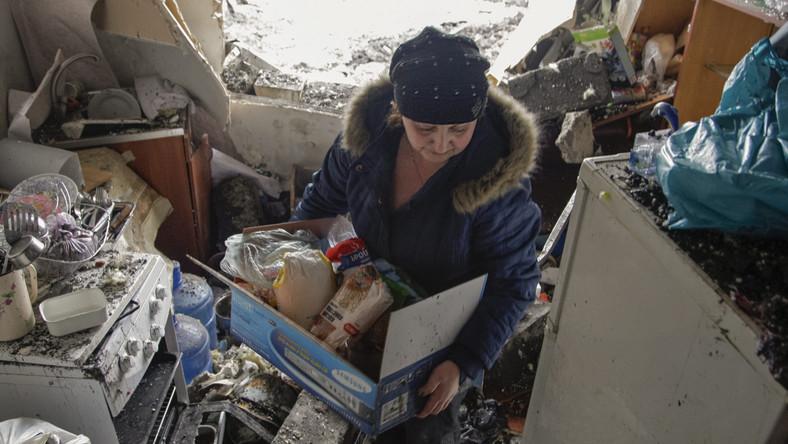 Mieszkanka zniszczonego domu w Doniecku wyjmuje z zamrażarki pozostawione tam jedzenie.