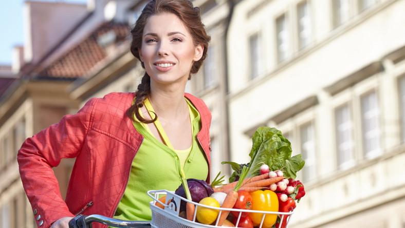 Kobieta ne rowerze wiezie warzywa. Nowalijki