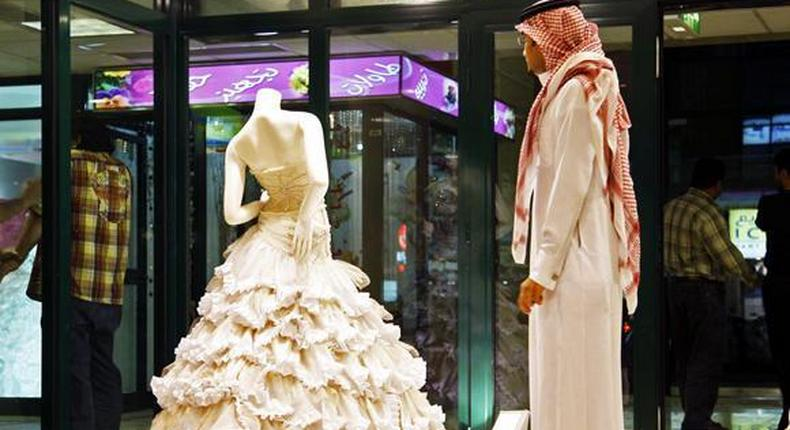 In this Aug. 3, 2008 file photo, a Saudi man stands in front of a wedding dress at a shop in Riyadh, Saudi Arabia.