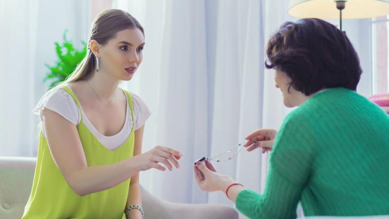 Kobieta daje drugiej kobiecie naszyjnik - talizman