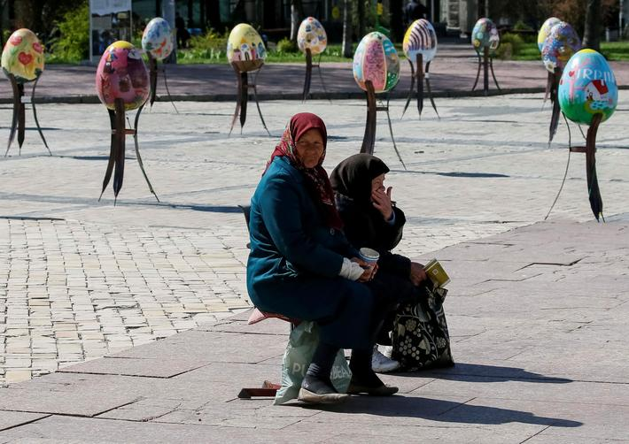 "Elderly women beg for money near traditional Ukrainian Easter eggs ""Pysanky"", displayed at square, a"