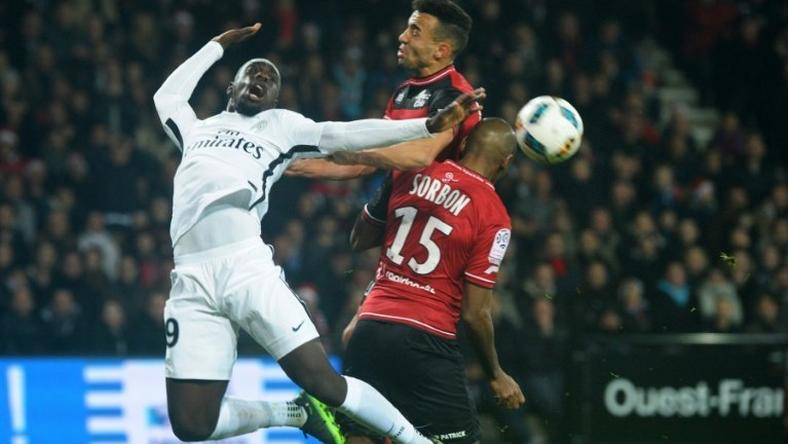 Paris Saint-Germain's Jean-Kevin Augustin (L) vies with Guingamp's Jeremy Sorbon (R) on December 17, 2016 at the Roudourou stadium in Guingamp, western of France