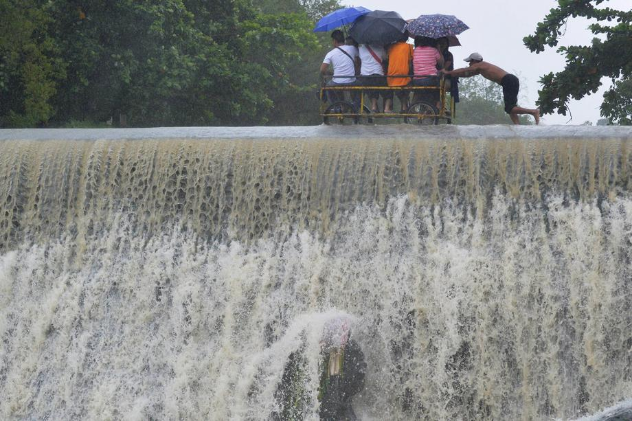 Residents cross a swelling dam, due to rising waters brought about by Typhoon Koppu, in Las Pinas ci