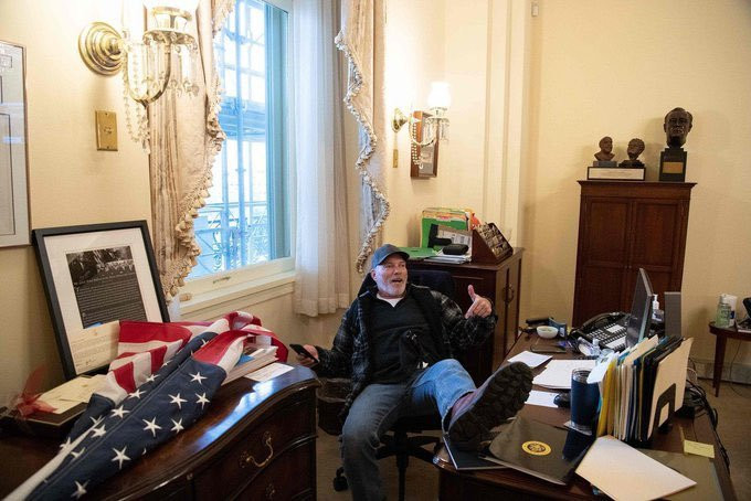A Trump rioter takes the seat of House Speaker Nancy Pelosi (AP/Reuters)