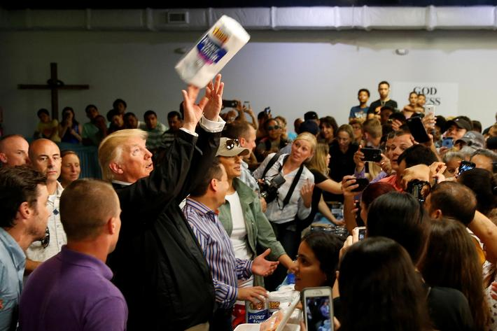 U.S. President Trump tosses rolls of paper towels to people at a hurricane relief distribution cente