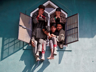 People react as they sit in a window of a mosque during the funeral of Tauseef Ahmad Wagay, a suspec