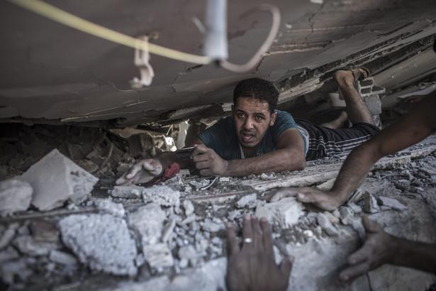 Palestyńczycy przeszukują gruzy w Strefie Gazy. Fot. EPA/OLIVER WEIKEN