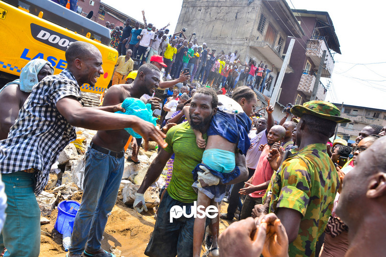 A jubilant crowd cheers as a conscious girl is rescued (Pulse)