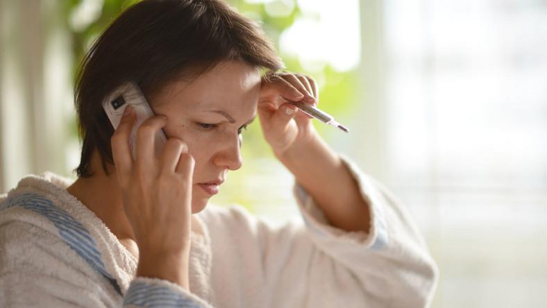 Chora kobieta dzwoni przez telefon, teleporada