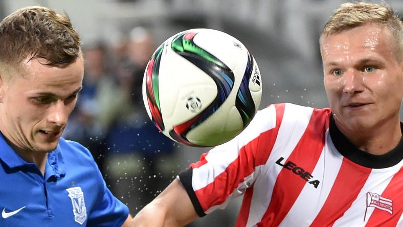 Zawodnik Cracovii Kraków Paweł Jaroszyński (P) walczy o piłkę z Tomaszem Kędziorą (L) z Lecha Poznań podczas meczu polskiej Ekstraklasy