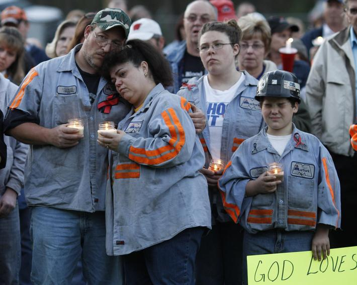 Mourners comfort each other during a candle light vigil in Montcoal