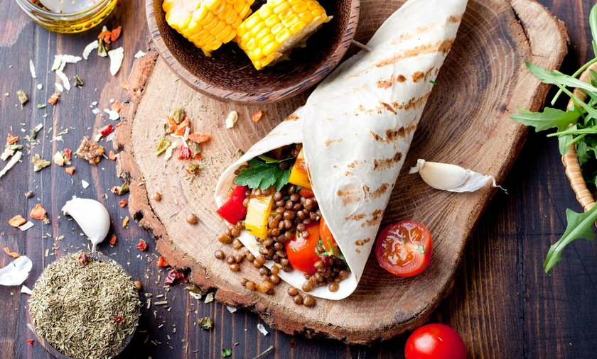 Vegan tortilla wrap, roll with grilled vegetabes, lentil, corn cob.