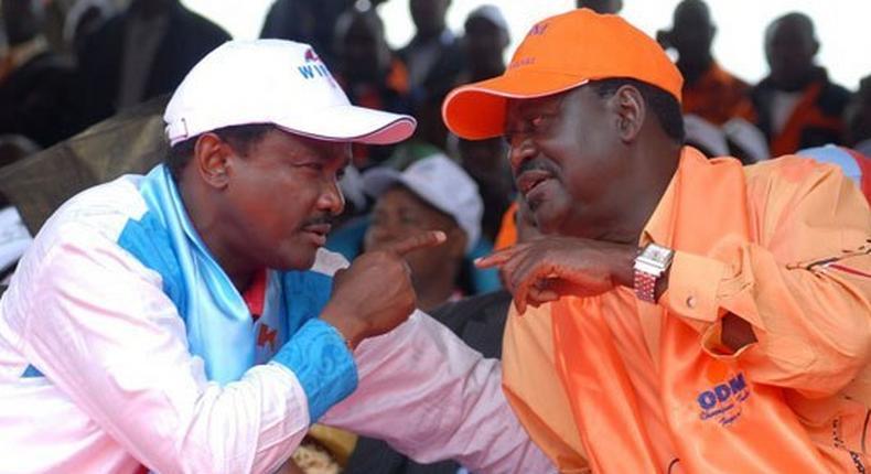 Kalonzo Musyoka speaks with Raila Odinga during the Cord rally at Uhuru Park in Nairobi on December 22, 2012.