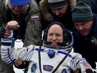 Ground personnel help U.S. astronaut Scott Kelly to get out of a Soyuz capsule shortly after landing