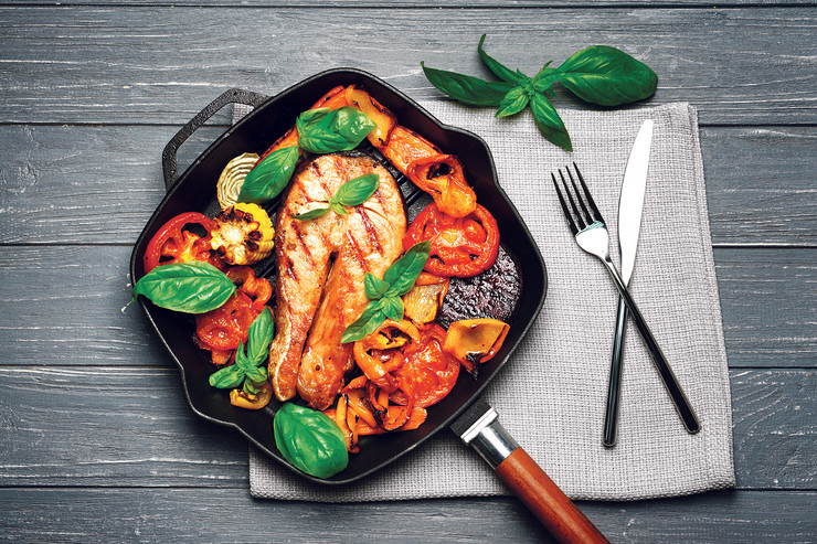 stock-photo-iron-cast-pan-with-slice-of-red-fish-and-vegetables-on-napkin-546744496