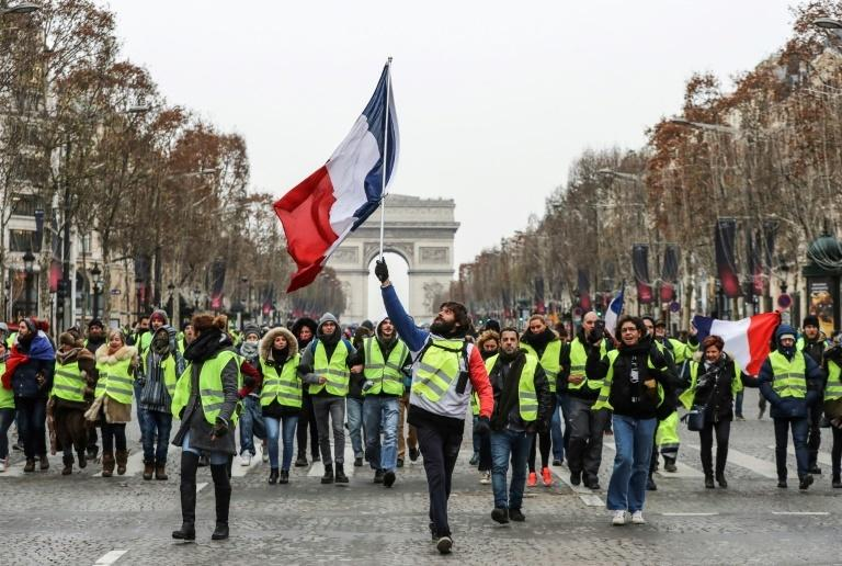 A protester wearing a yellow vest waves the French national flag during a demonstration against rising costs of living blamed on high taxes on the Champs-Elysees in Paris, on December 15, 2018