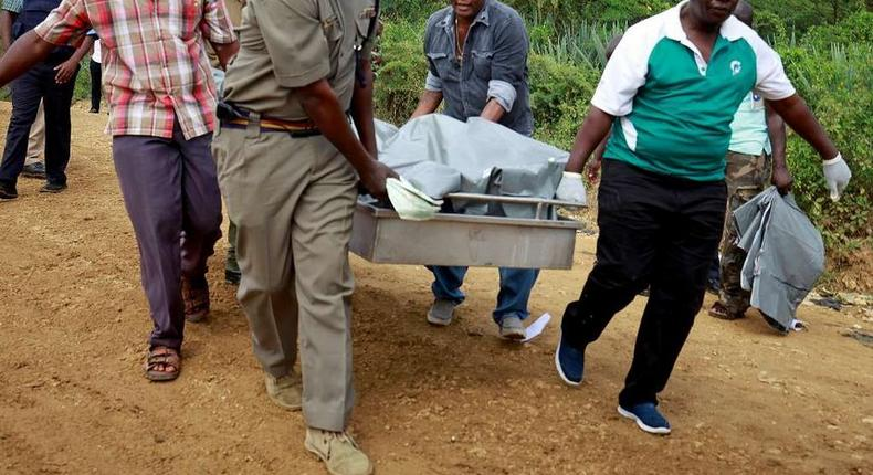 Policemen carry the dead bodies
