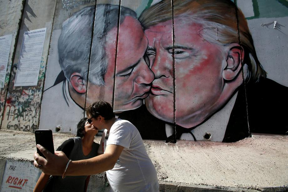 Tourists kiss each other as they stand in front of a mural depicting U.S. President Donald Trump and