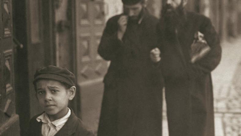 """Mały chłopiec wchodzący do bramy domu przy ul. Świętojerskiej 5 wraca z zajęć w chederze, trzymając pod pachą książkę. Za jego plecami przechadza się para studentów jesziwy, z powagą dyskutujących na tematy talmudyczne. Radosny, wolny od nauki w szkołach religijnych 33 dzień omeru, czyli siedmiotygodniowego okresu liczonego pomiędzy świętami Pesach i Szawuot, wypadał w pierwszych dniach maja i zwał się lag ba-omer, z czego wzięła się znana ze współczesnej gwary uczniowskiej """"laba"""". Fotografia z września 1926 r. Wydawnictwo RM"""