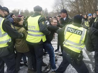 Police officers attempt to calm down people during a protest at the Danish-German border in Krusaa