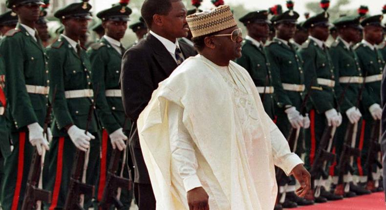 Former Nigerian President General Sani Abacha walks past a line of military troops March 23 during the departure ceremony for Pope John Paul II who was ending a three day visit to the country. NIGERIA POPE (Reuters)