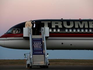 Republican presidential nominee Donald Trump waves as he walks off his plane at a campaign rally in