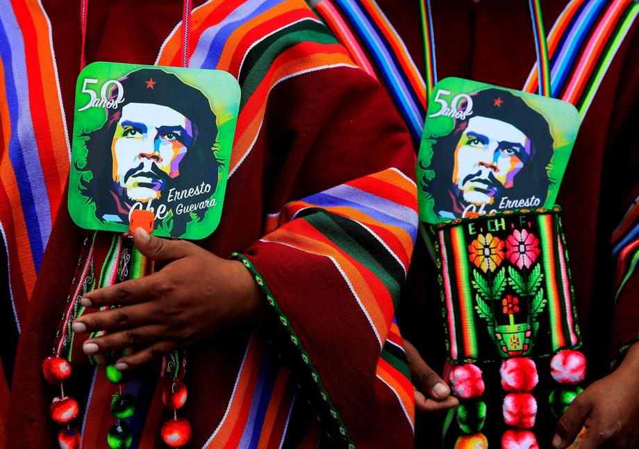 Aymara men hold images of Ernesto Che Guevara as they attend a ceremony to commemorate Che Guevara's