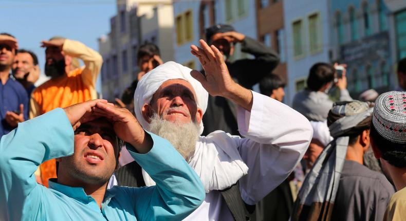 People look up at a dead body hanged by the Taliban from a crane in the main square of Herat city in western Afghanistan, on Saturday, September 29, 2021.