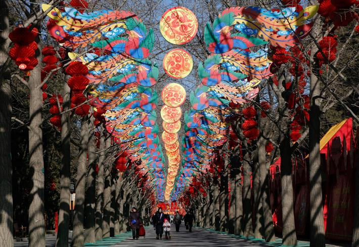 Visitors walk beneath decorations set up for the upcoming Spring Festival celebrations in Ditan Park