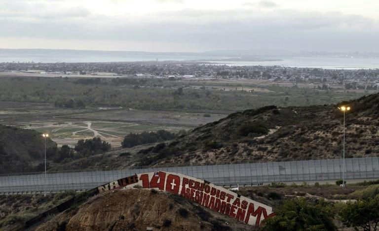 """140 Journalists Murdered in MX (Mexico)"" reads the words painted on the Mexico-US border fence section in Tijuana, Mexico in May 2018"
