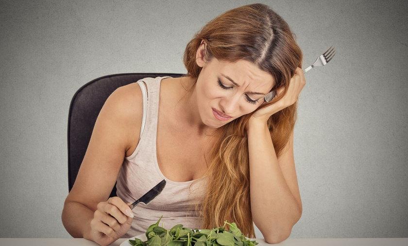 kobieta z niesmakiem jedząca sałatkę
