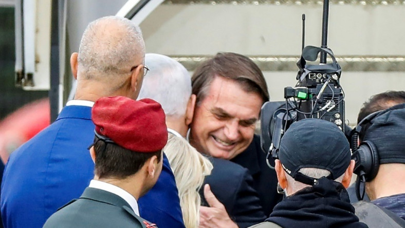Brazilian President Jair Bolsonaro (C), seen here being embraced by Israeli Prime Minister Benjamin Netanyahu, is in Israel on a visit while at home protesters marched against his government