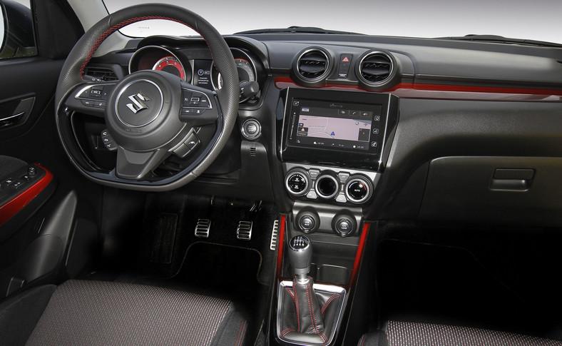 Wersję Sport w środku poznasz o podciętej o dołu kierownicy, głębokich fotelach i czerwonych dodatkach. Suzuki nie poskąpiło elektronicznych bajerów. Lista obejmuje adaptacyjny tempomat czy system wykrywania zygzakowania np. z powodu senności kierowcy. Standardowe wyposażenie obejmuje system nawigacji z siedmiocalowym wyświetlaczem dotykowym (kompatybilny z Apple CarPlay i Android Auto). Klimatyzacja automatyczna także jest w cenie