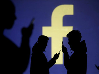 FILE PHOTO: Silhouettes of mobile users are seen next to a screen projection of Facebook logo in thi