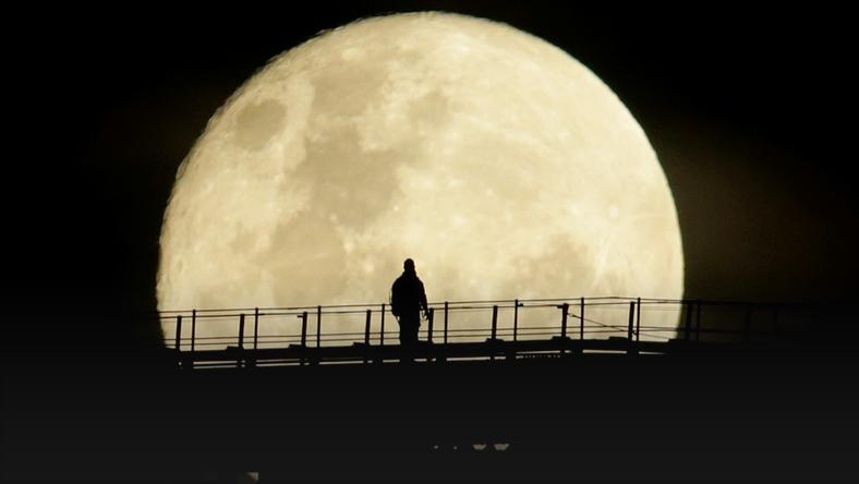 A man walks on the top span of the Sydney Harbour Bridge as the supermoon enters its final phase in Sydney
