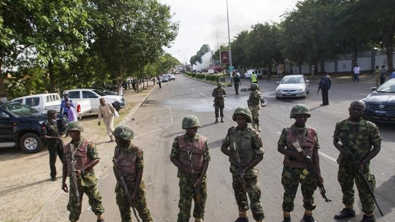 Nigerian army soldiers stand guard as they cordon off a road leading to the scene of a blast at a business district in Abuja June 25, 2014. REUTERS/Afolabi Sotunde