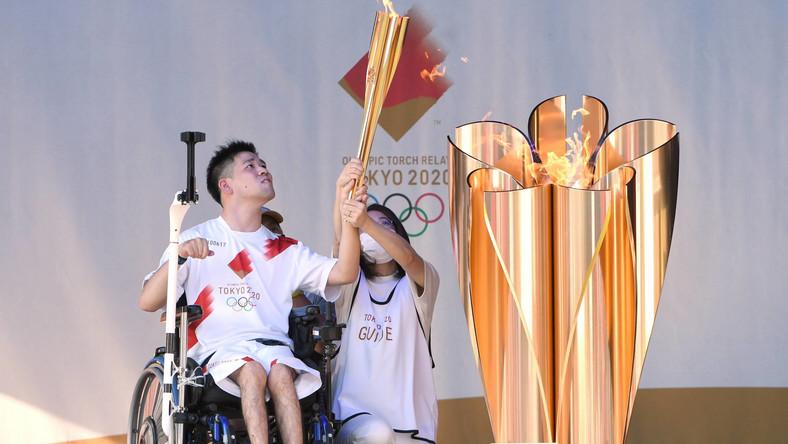 Niepełnosprawny mężczyzna na wózku inwalidzkim z ogniem olimpijskim w Tokio