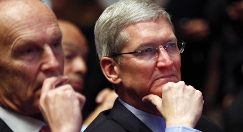 Apple CEO Tim Cook listening to a Barack Obama speech