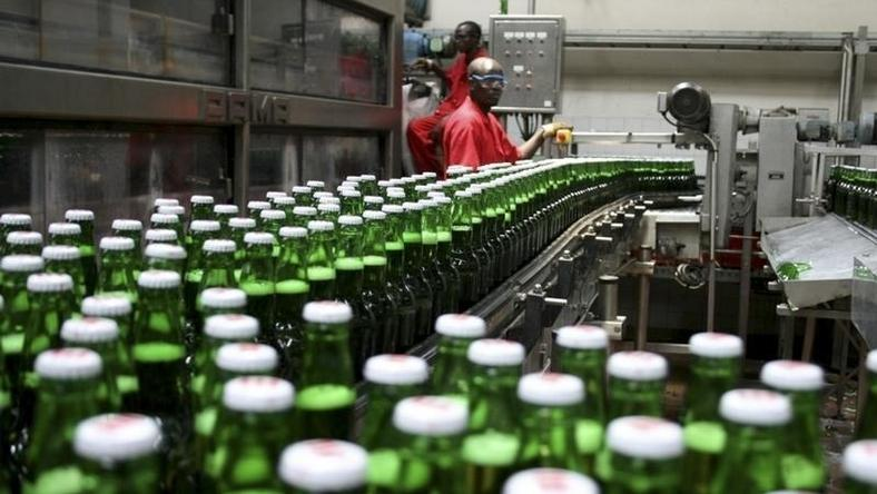 Technicians inspect beer bottles on a conveyor belt at a brewery in Gisneyi, western Rwanda, in a file photo. REUTERS/Hereward Holland