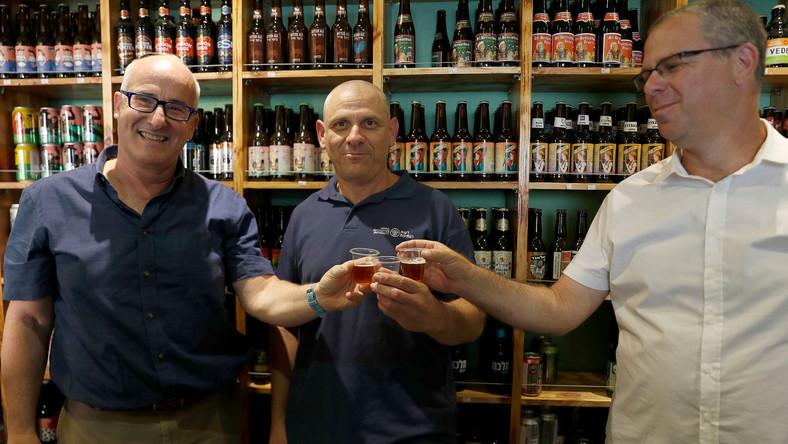 ProfesorAren Maeir (L) Dr Yitzhak Paz i profesor Yuval Gadot piją piwo zrobione ze starożytnych drożdży
