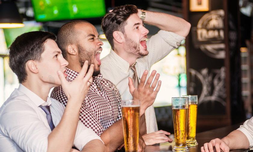 koledzy oglądają mecz w pubie