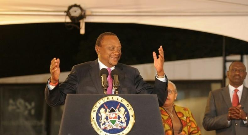 Kenya's President Uhuru Kenyatta (L), flanked by his wife Margaret Gakuo Kenyatta (2-L), speaks following the Electoral Commission's official announcement declaring him the winner of the August 8 election